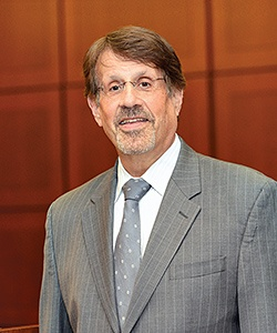 Richard Kling wearing a gray suit and tie with white shirt, standing in front of a brown paneled wall.