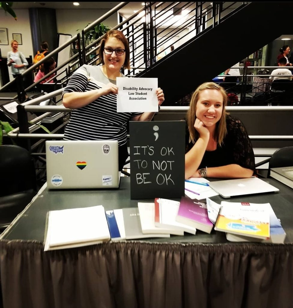 Natasha Crespo and Kelsie Neahring at Fall 2019 student organization fair. Natasha is holding a sign that says Disability Advocacy Law Student Association. There is a black sign that says ; It's okay to not be ok. There are health law books and journals on a table.