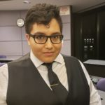 Photo of Gabrielle Robles standing in a classroom while wearing a white button-up, a black vest, a black tie, a silver tie clip, and black-framed glasses