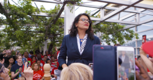 Photo of Rashida Tlaib looking off into the distance as she speaks to a crowd