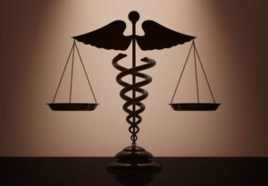 illustration for website sidebar of scales with Caduceus symbol for healthcare in the center.